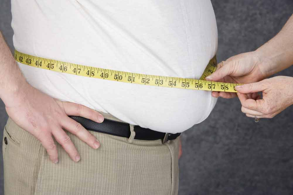 Man with obese stomach being measured