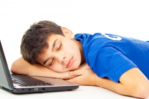 Young teenage boy in blue shirt resting his head on his arm asleep on computer laptop