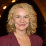 Medium shot of TPT reporter Mary Lahammer with blond hair and rose colored jacket