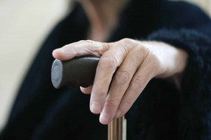 Elderly woman's hand on a cane.