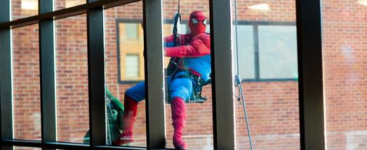 Window washer in Spiderman costume cleaning large hospital window