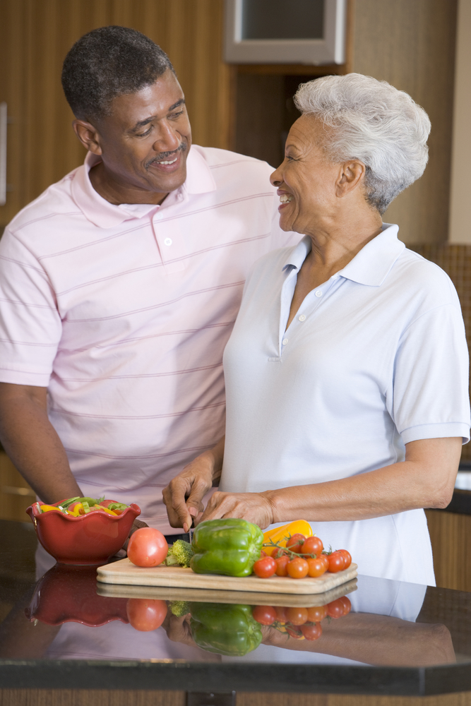African American senior couple in light colored polo shirts standing at a kitchen counter with fruits and vegetables