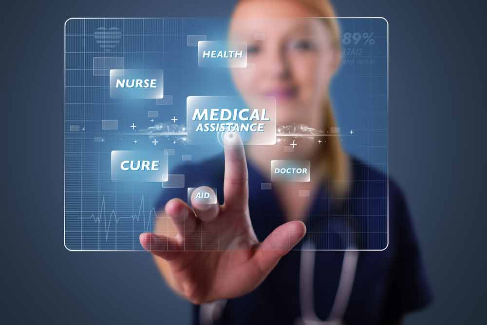"""Nurse with blonde hair in navy scrubs pressing a button on a clear screen that reads, """"Medical Assistance"""""""