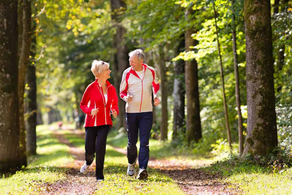 Senior woman and man running on dirt path through green forest