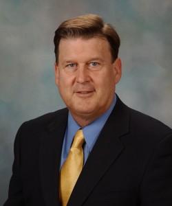 Medium shot of Dr. Thomas Brott in dark suit and yellow tie