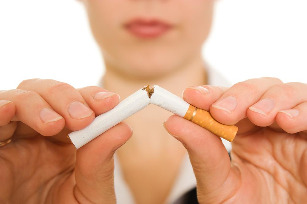 Closeup of caucasian woman's hands breaking a cigarette in half