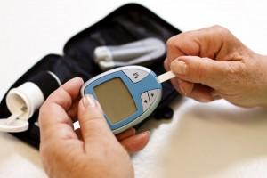 caucasian person checking blood sugar counter for diabetes