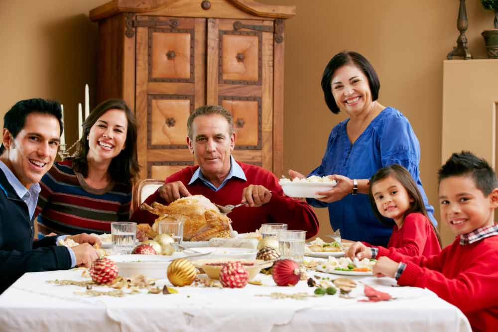 multi-generational Latino family at holiday dinner table with a turkey