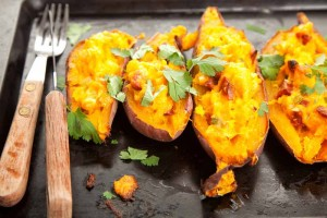 stuffed sweet potatoes cut in half on cooking tray with fork and knife on the side
