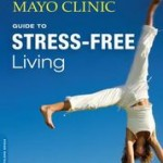 Mayo Clinic Stress-Free book cover with blue sky and woman in white exercise outfit doing a handstand