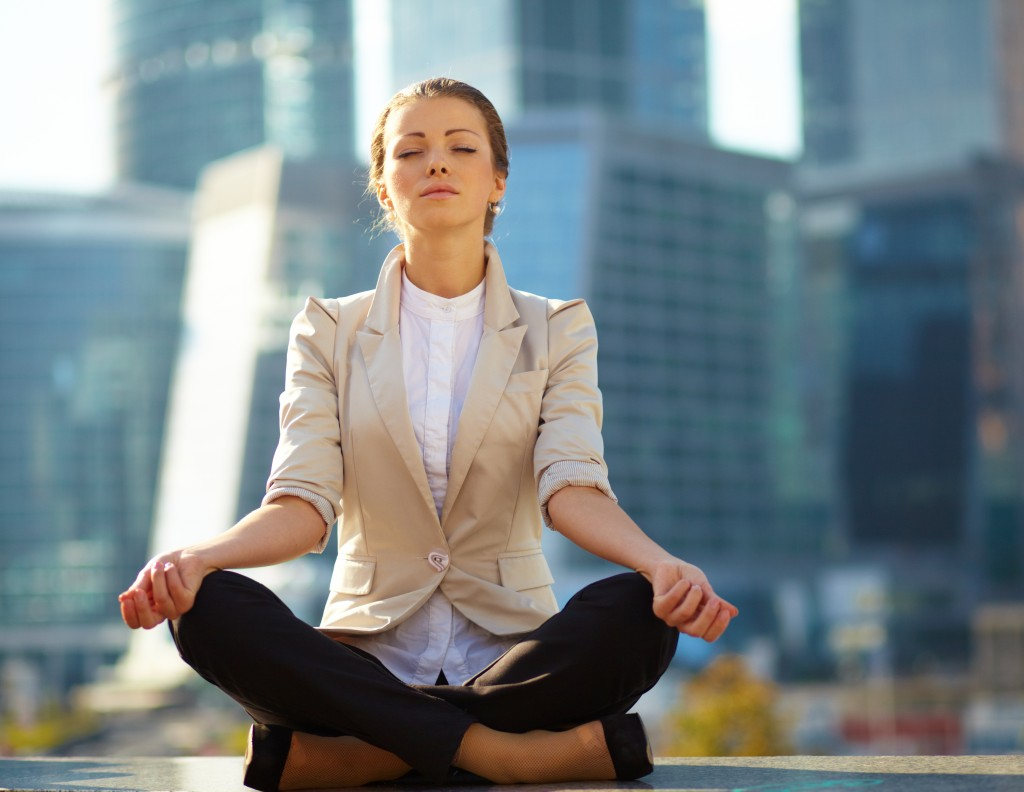 Caucasian business woman meditating with the city skyscrapers in the background