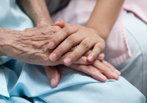 Young girl's hands holding older woman's hands in a hospital bed.