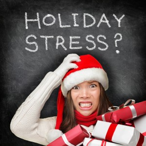 Holiday Stress chalkboard with woman in red santa hat and holding presents