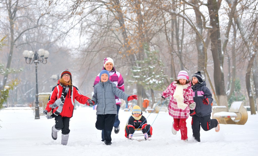 Children bundled up in winter clothes sledding and playing in the snow
