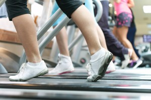 three or four women's legs running in tennis shoes on treadmills
