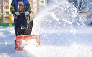 Man in blue vest pushing orange and black snowblower