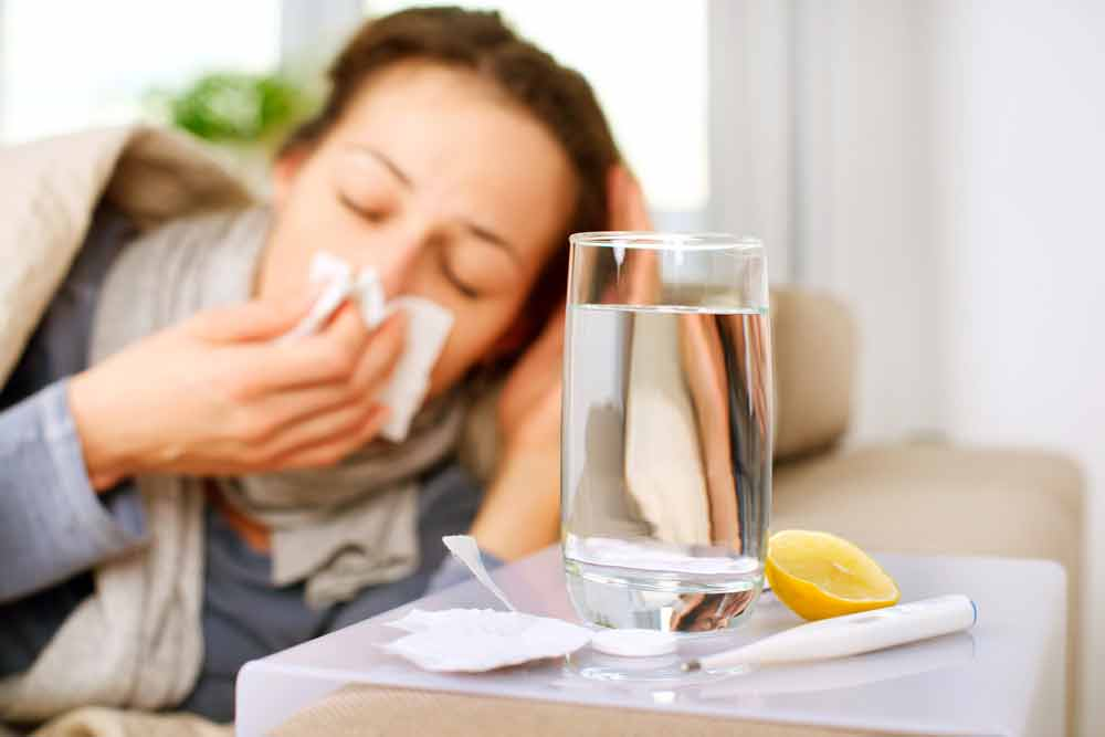 Caucasian woman bundled up on couch sneezing into a tissue with a glass of water on a table