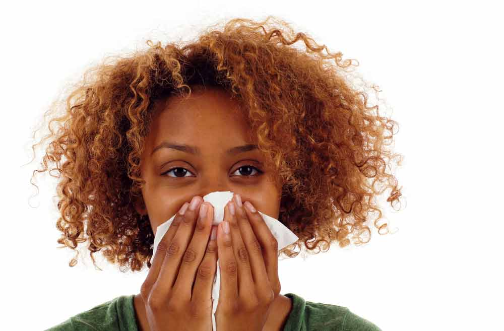 African American woman coughing and sneezing into tissue