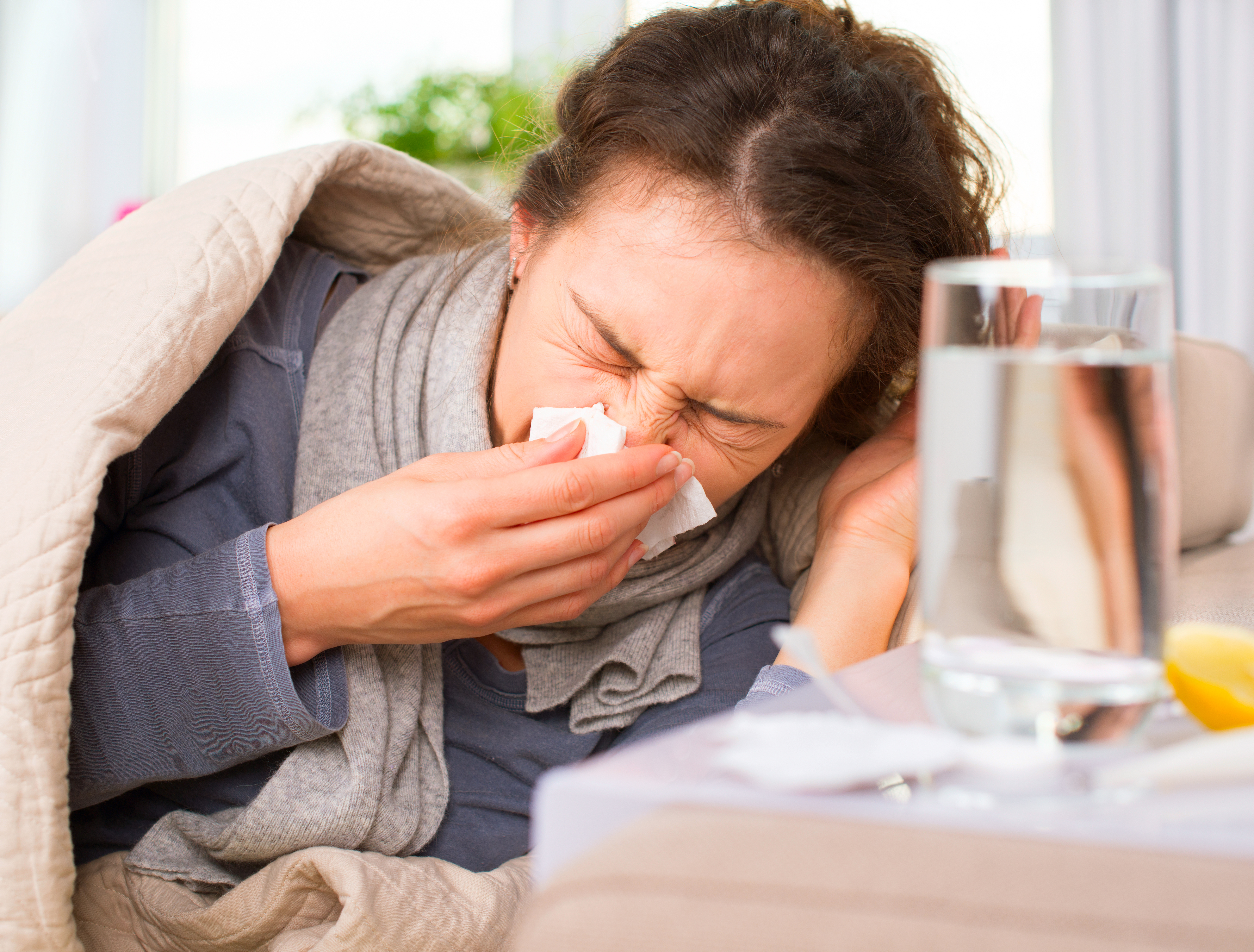 Woman sneezing and coughing with a cold of flu