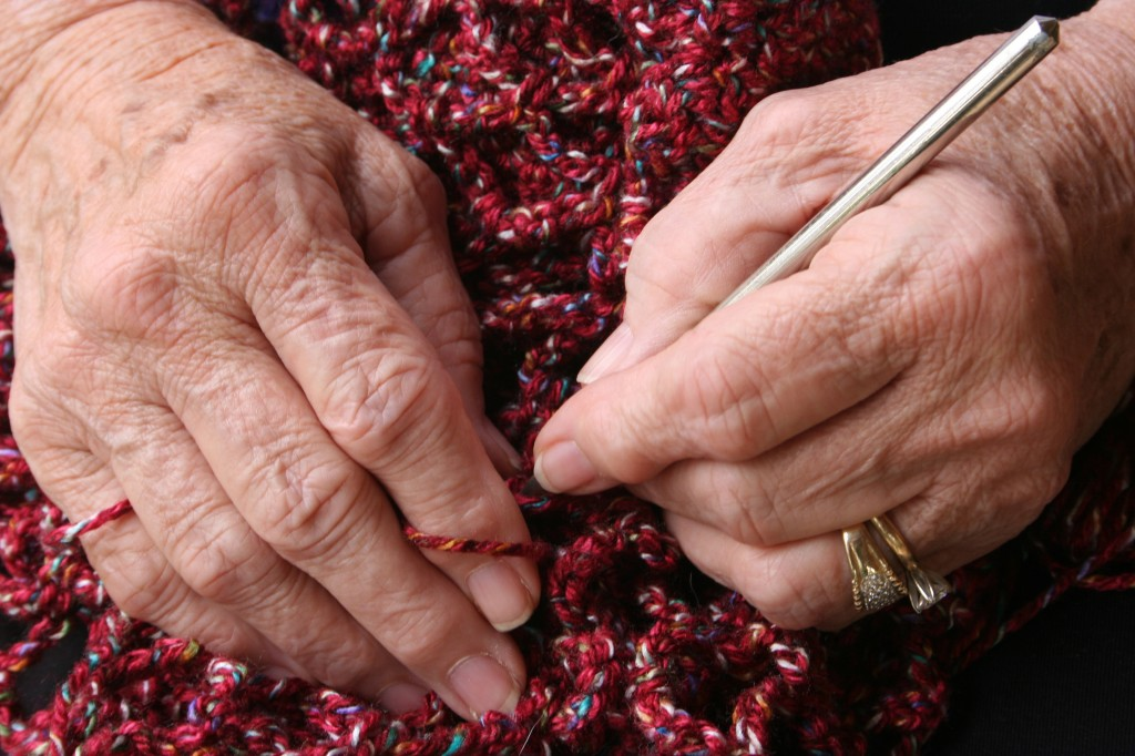 Close up of arthritic hands knitting a woolen shawl