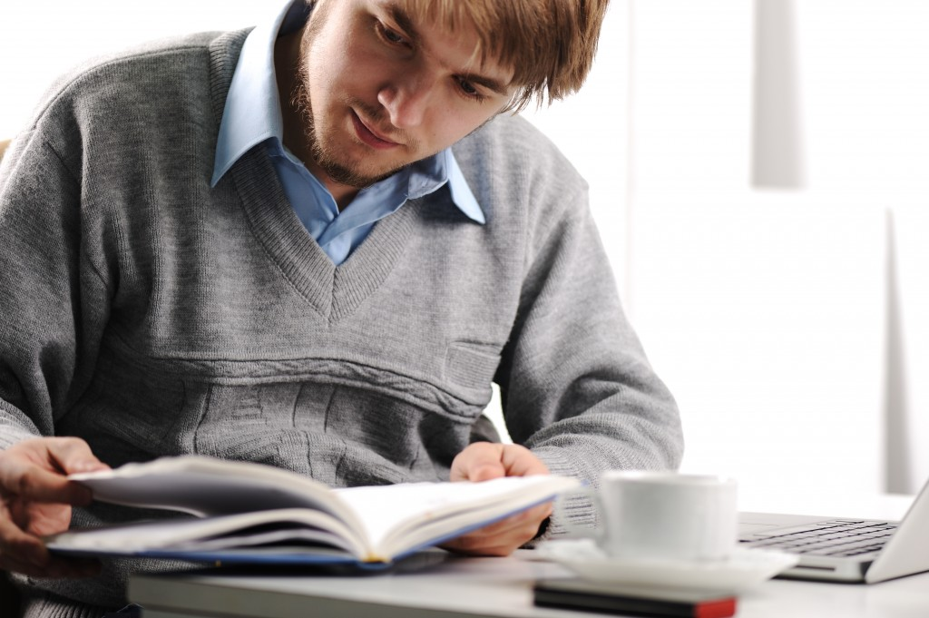 Man reading book with laptop computer on table