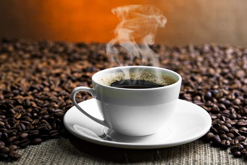 Steaming cup of coffee with coffee beans