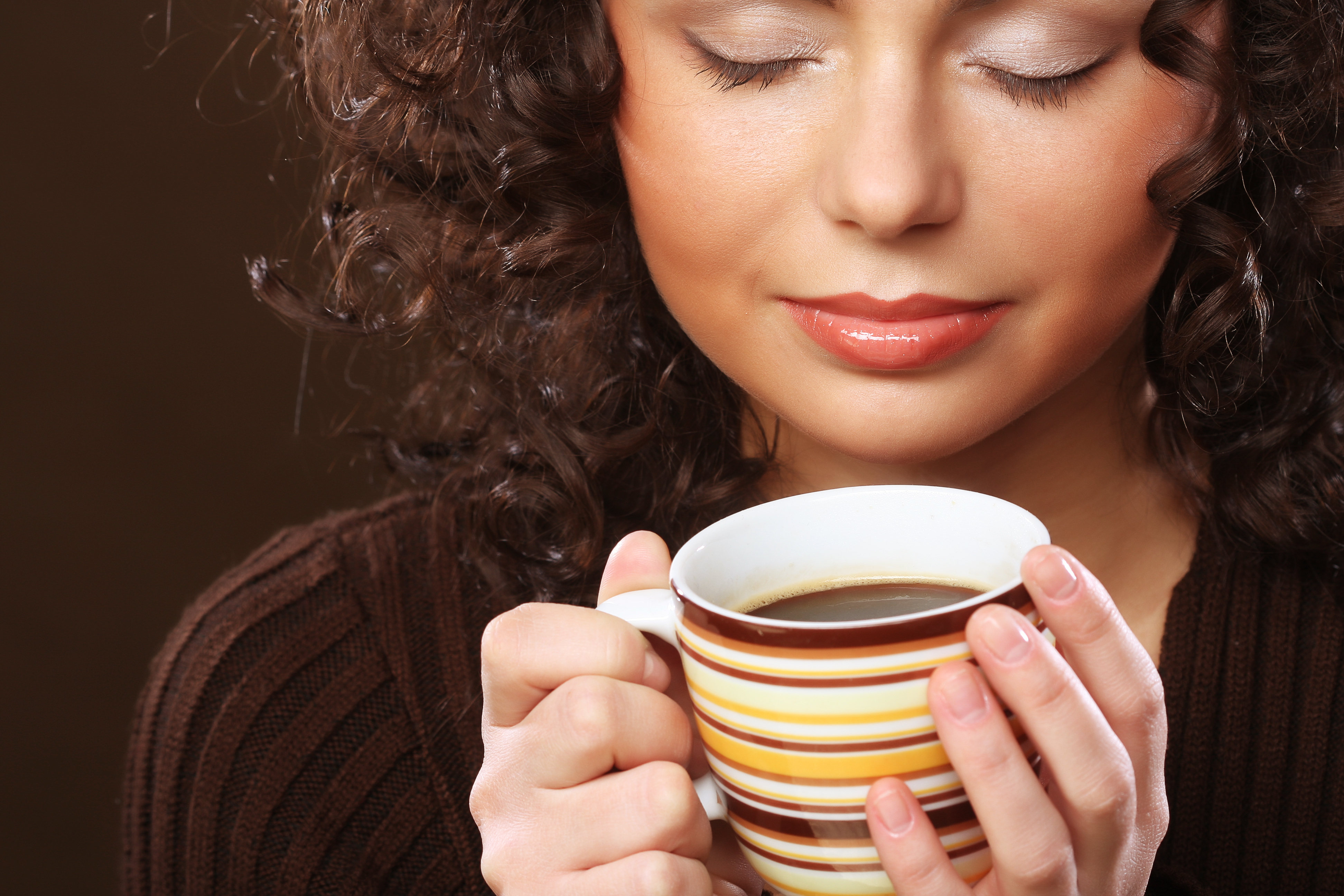 Woman holding cup of coffee with both hands and eyes closed.