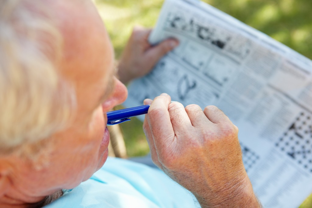 Older man working on a crossword puzzle.