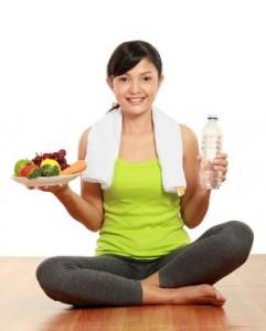 Una mujer con buen estado físico que tiene comida y agua en las manos