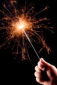 child's hand holding a sparkler
