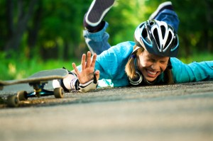 Young girl lying on ground from skateboard accident