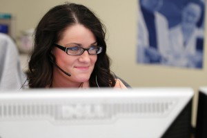 Woman with glasses on computer at call center