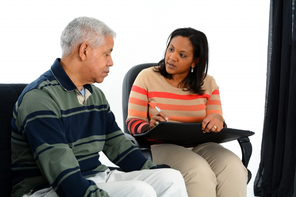 Aging man or father with care giver or relative taking medical notes