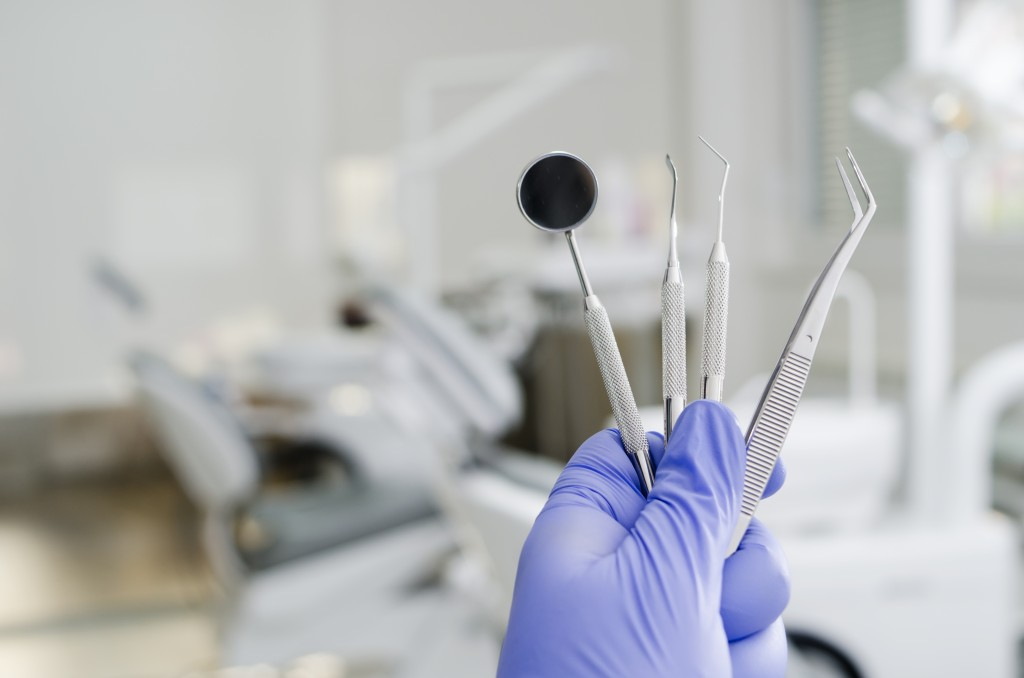 gloved hand holding dental tools to exam teeth