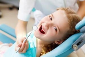 Niña pequeña sentada en el sillón dental