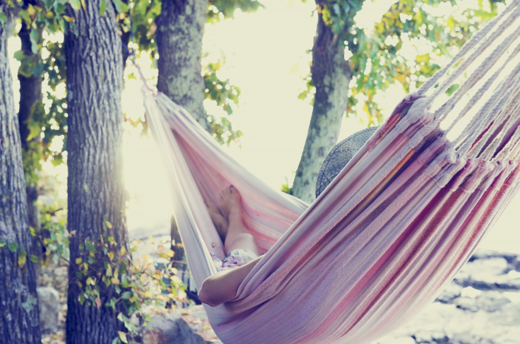 woman resting in a tree hammock in the shade on a hot summer day