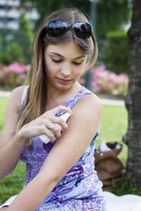 woman putting bug spray on her arm