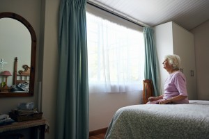 senior citizen, older woman sitting alone and looking out window