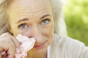 close-up of older woman dabbing her eyes with a tissue