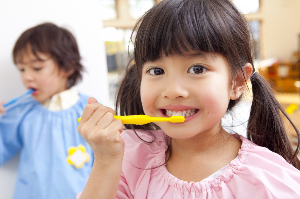 young girl brushing her teeth for good oral health