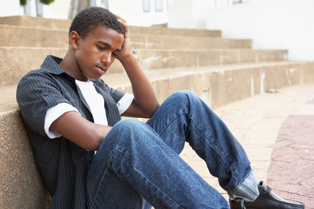 unhappy male teenage student sitting outside on college steps