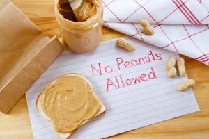 """Letrero para alergia alimentaria que dice """"no se permite el maní"""", colocado junto a un frasco de mantequilla de maní"""