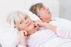 Un hombre ronca y la mujer se cubre los oídos para intentar dormir