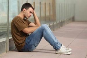 Muchacho adolescente con apariencia triste, sentado en el suelo con la mano en la cabeza