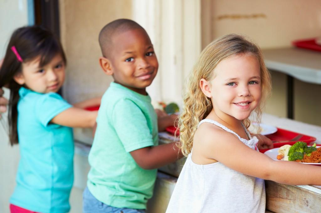 three schoolchildren in cafeteria lunch line