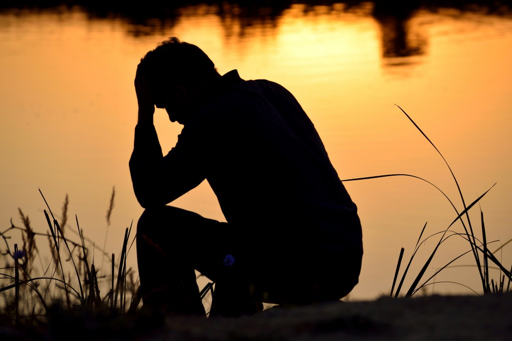 silhouette of lonely, depressed man sitting by lake
