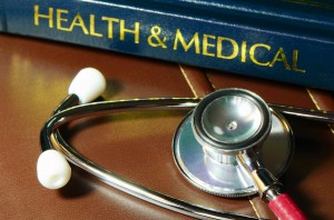 stethoscope and book binding with words health and medical on table