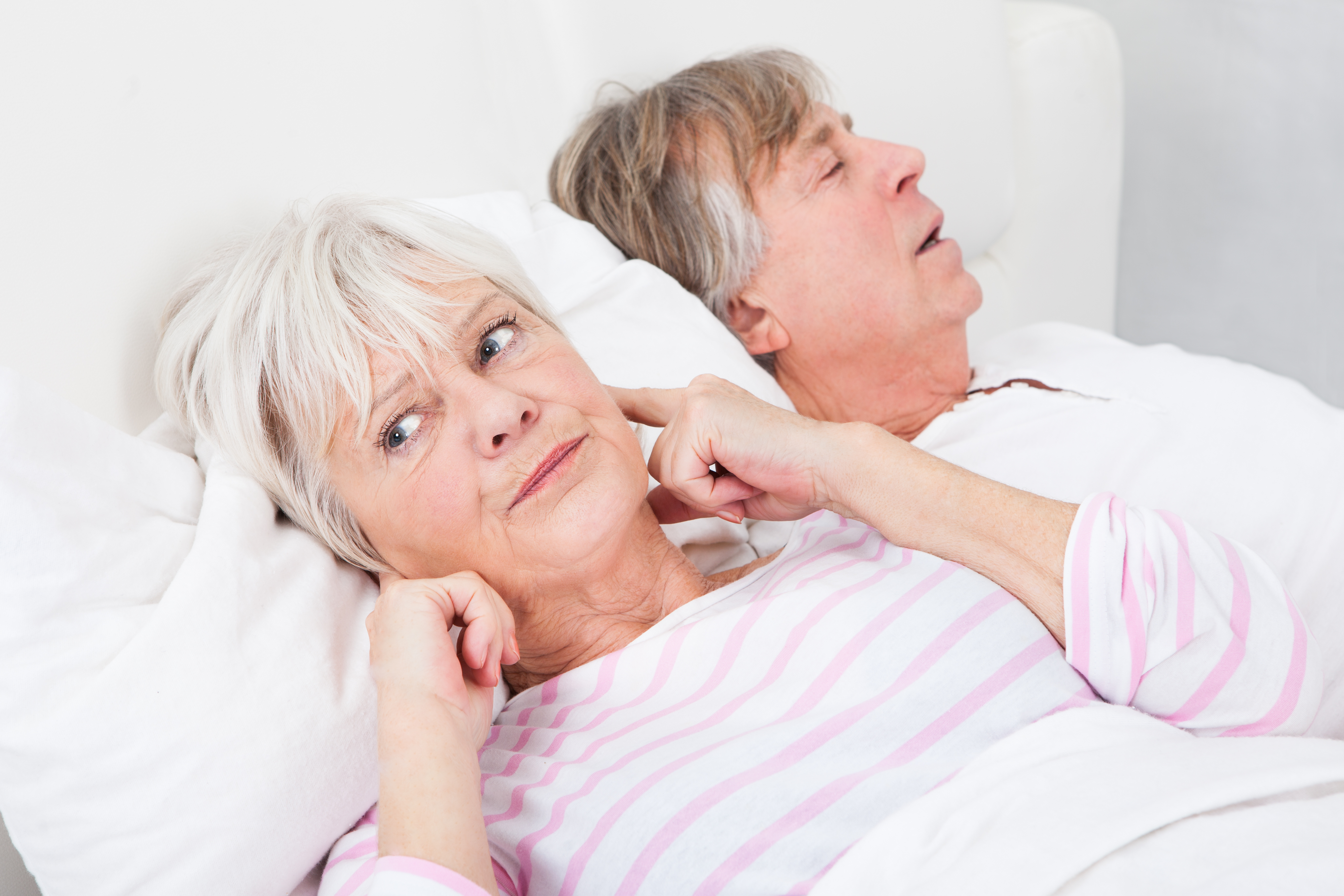 man snoring and woman covering her ears trying to sleep