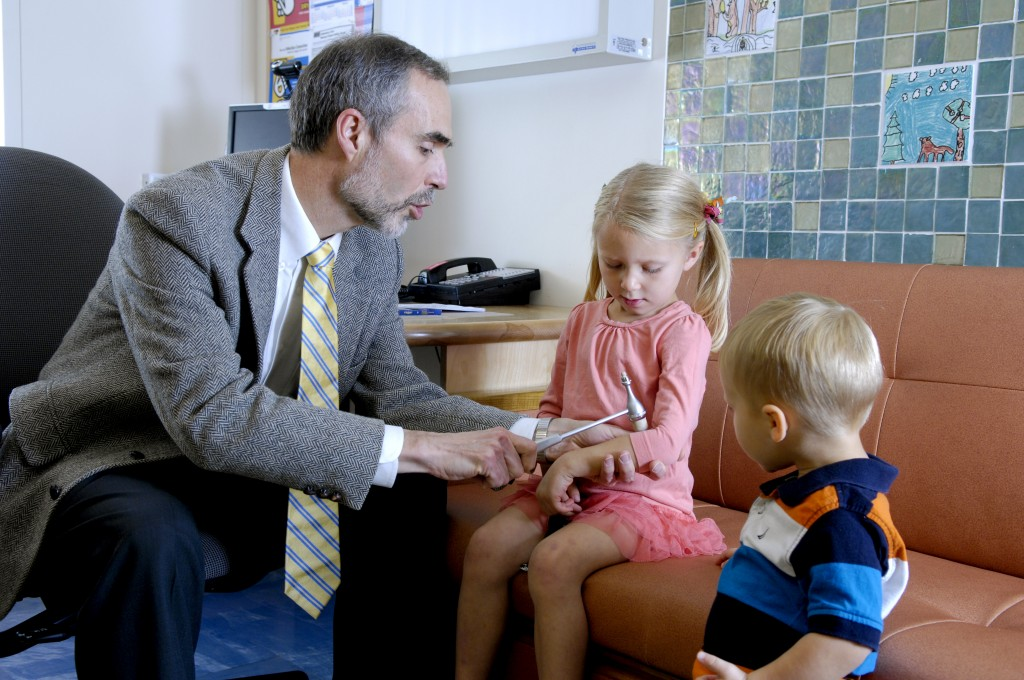 physician talking with two children