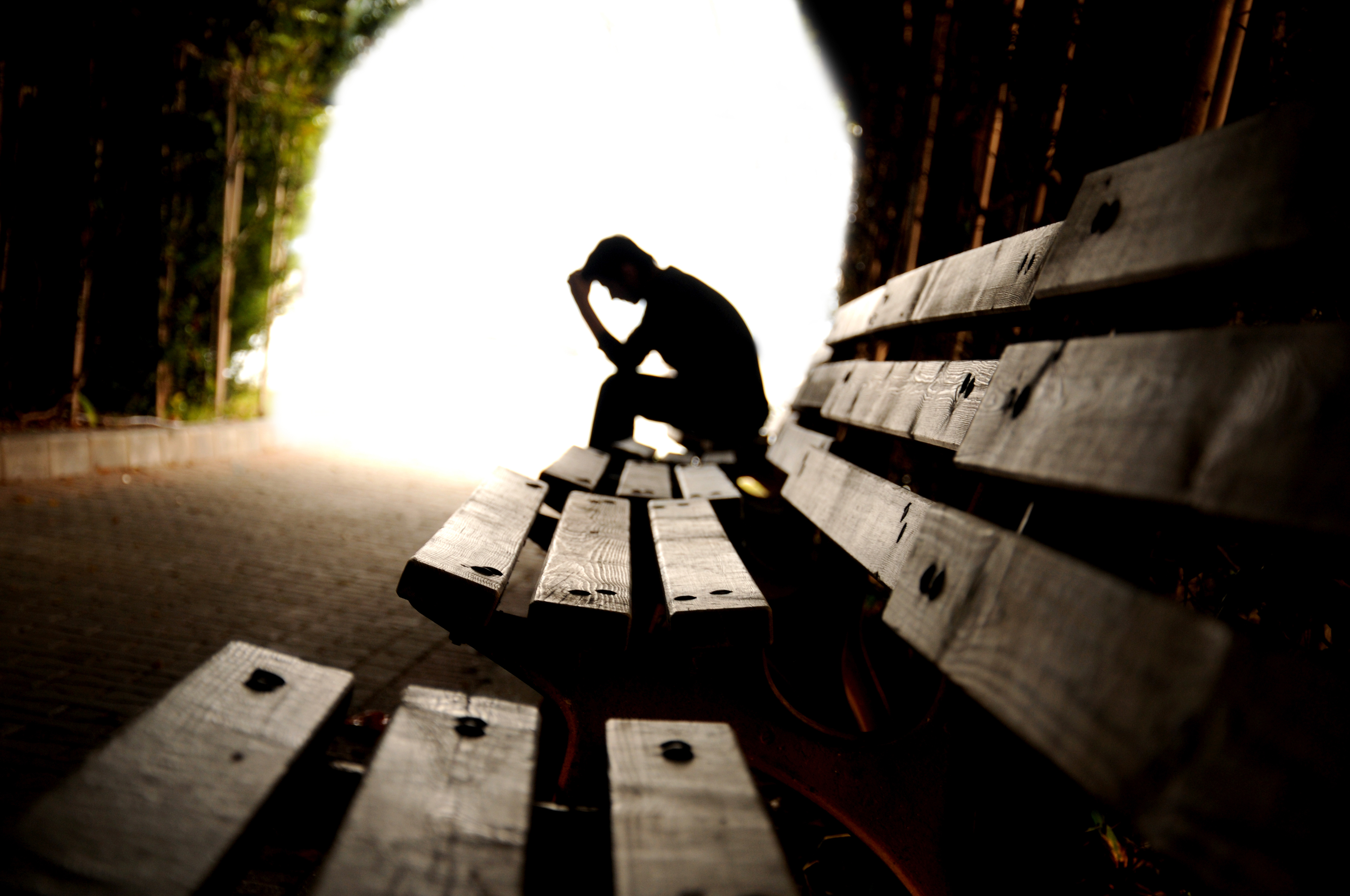 a lonely man sitting on a park bench